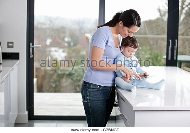 A mother and baby son looking at a digital tablet - Stock-Bilder