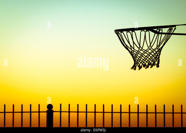 Basketball hoop on beach at sunrise. - Stock Image