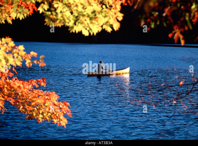 A man canoes around Bear Lake in the mountains of North Carolina in the fall - Stock Image
