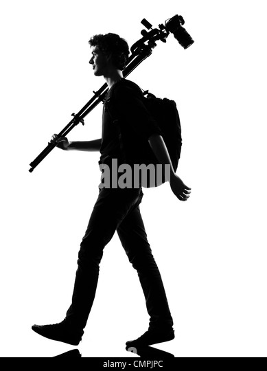 young man photographer silhouette in studio isolated on white background - Stock Image