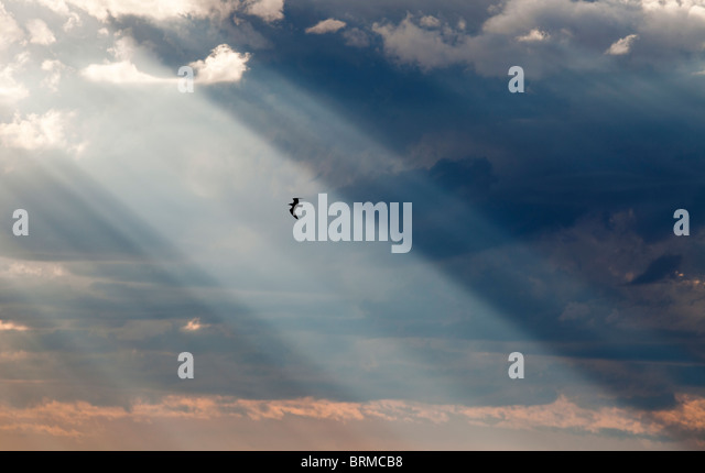 Sun shining through dark clouds - Stock Image