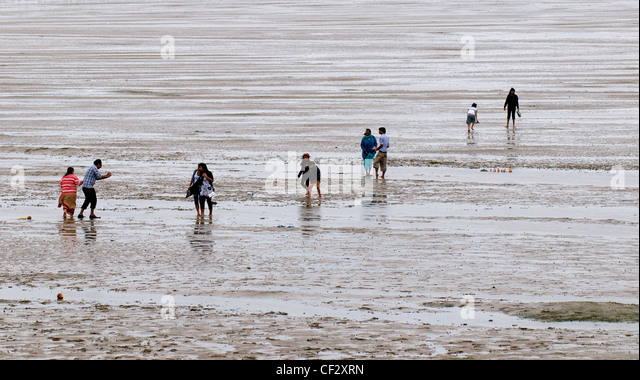 People walking on the foreshore of the Thames Estuary. - Stock Image