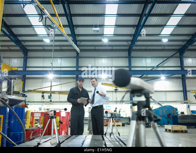 Office and factory worker checking sound volume in factory - Stock-Bilder
