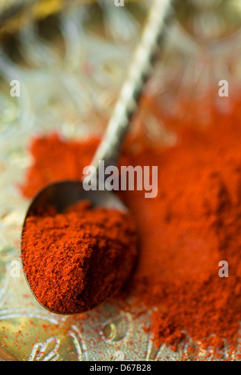 Ground paprika on plate with spoon - Stock Image