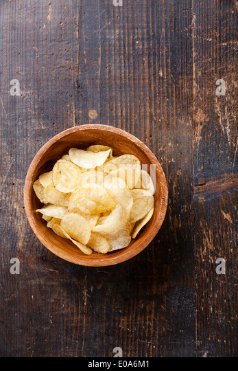 Crispy potato chips on wooden background - Stock Image