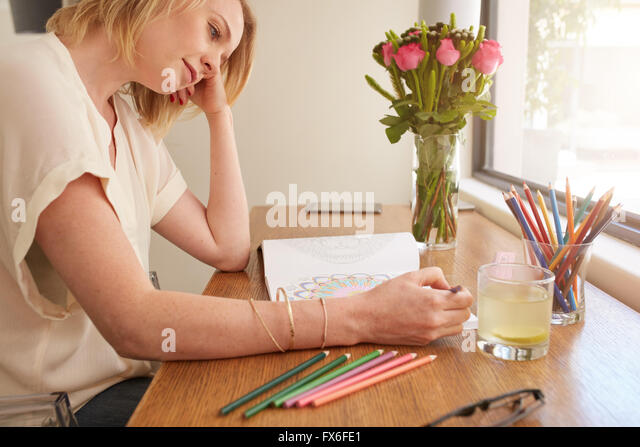 Woman drawing an adult coloring book while comfortably sitting at table by a window. - Stock-Bilder