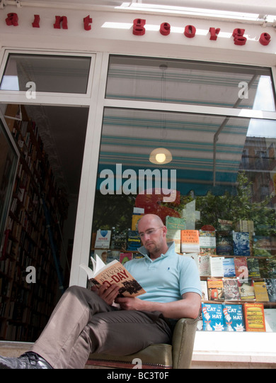 Man reading book outside secondhand bookshop called Saint Georges in bohemian Prenzlauer Berg in Berlin - Stock Image