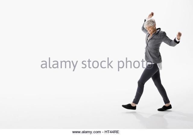 Energetic senior woman dancing against white background - Stock-Bilder