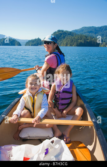 Mother and daughters rowing canoe on lake - Stock Image