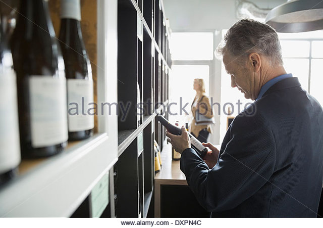 Man reading label on bottle in wine store - Stock Image