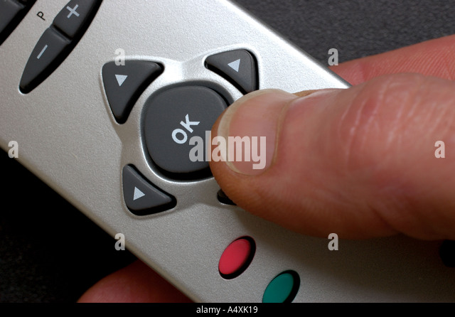 Hand holding remote control thumb pressing ok button - Stock Image