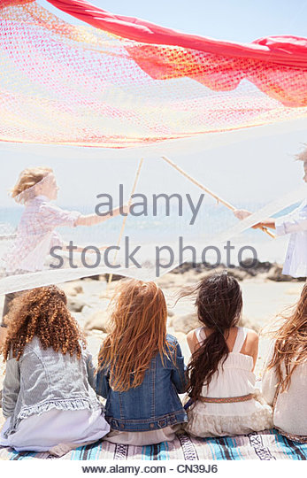 Girls sitting by fort on beach watching boys playfight - Stock Image