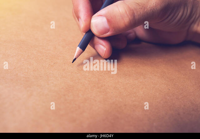 Male illustrator and sketch artist drawing with pencil, hand close up with selective focus - Stock Image