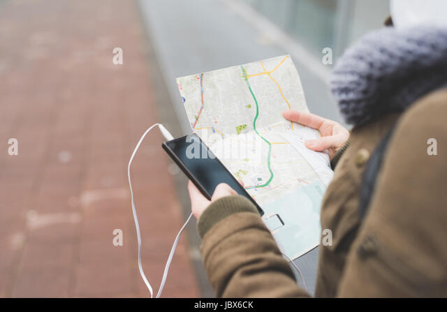 Over shoulder view of female backpacker with smartphone looking at map on city sidewalk - Stock-Bilder