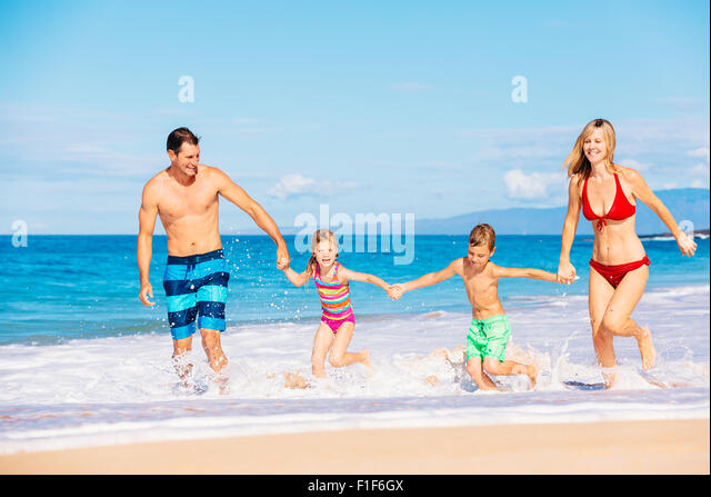 Family vacation. Happy family having fun on beautiful warm sunny beach. Outdoor summer lifestyle. - Stock Image