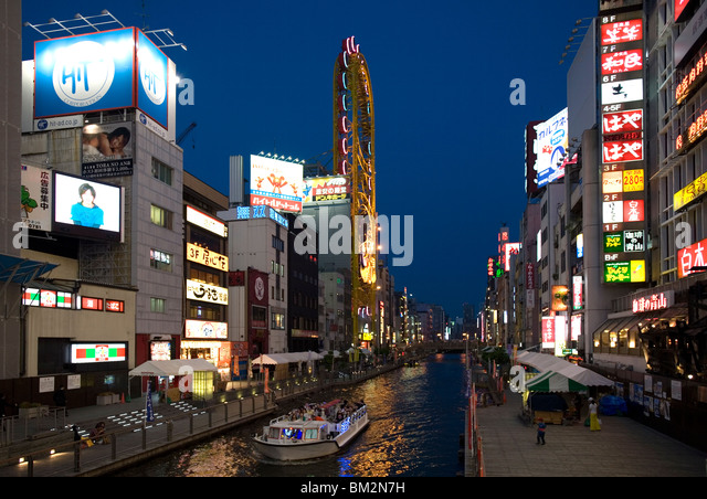 Tour boat on Dotonbori River glides past shops and restaurants in Namba, Osaka, Japan - Stock Image