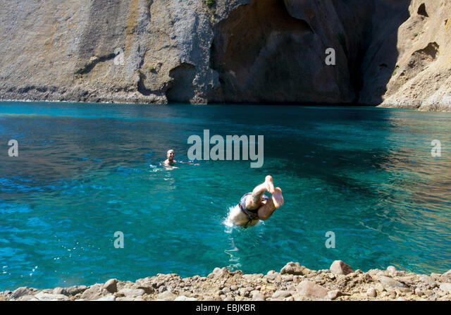 Two young men diving into sea and swimming, Marseille, France - Stock Image