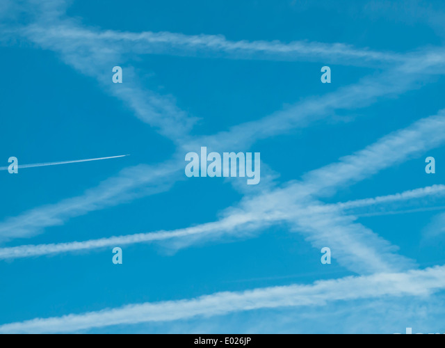 Pattern of many contrails/vapor trails of jet airplanes in the blue sky. - Stock Image