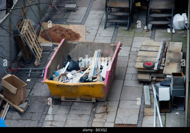 Builders skip half full in building site - Stock Image