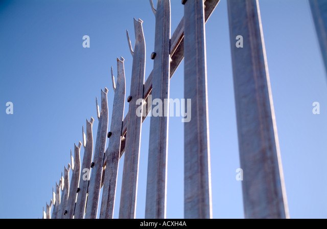 Abstract Metal security fencing disappearing into distance - Stock Image