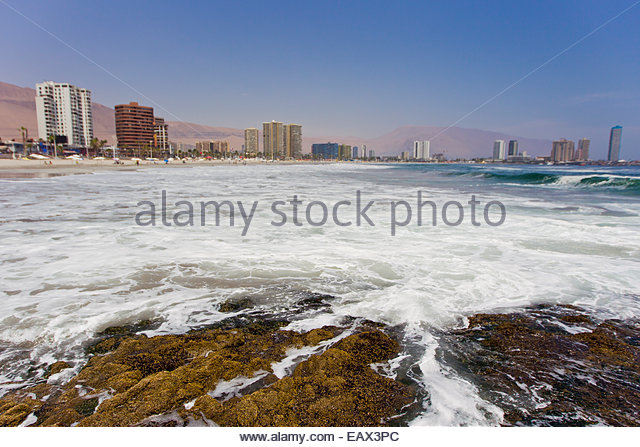 Waves crash on rocks on the Pacific coast of Iquique. - Stock Image