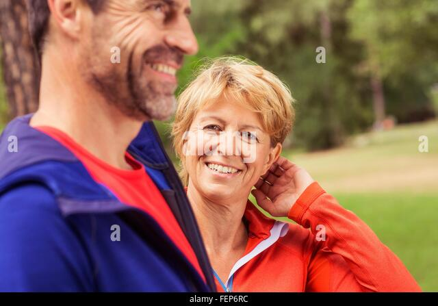 Couple wearing sports clothing, outdoors, smiling - Stock Image