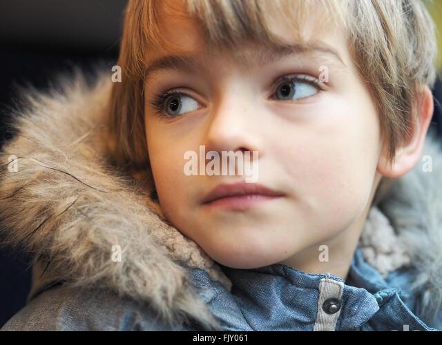 Close-Up Of Boy Wearing Fur Jacket In Car - Stock Image