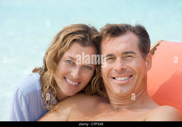Couple relaxing at beach, portrait - Stock Image