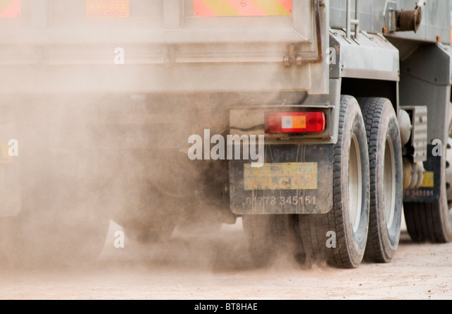 lorry kicking up dust dusty road roads earth mover truck trucks fine powdery fine - Stock Image