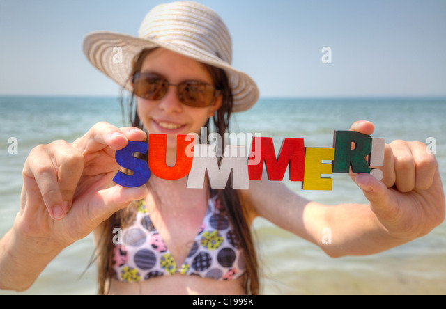 Teen girl at a beach with word 'Summer!' - Stock Image