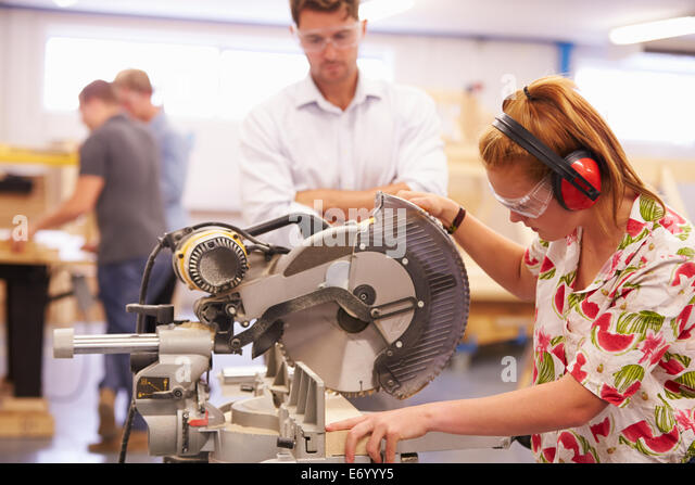 Student And Teacher In Carpentry Class Using Circular Saw - Stock-Bilder