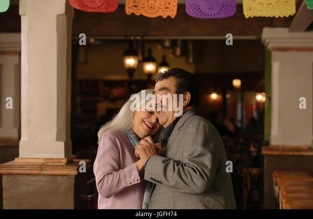 Older couple dancing in restaurant - Stock Image