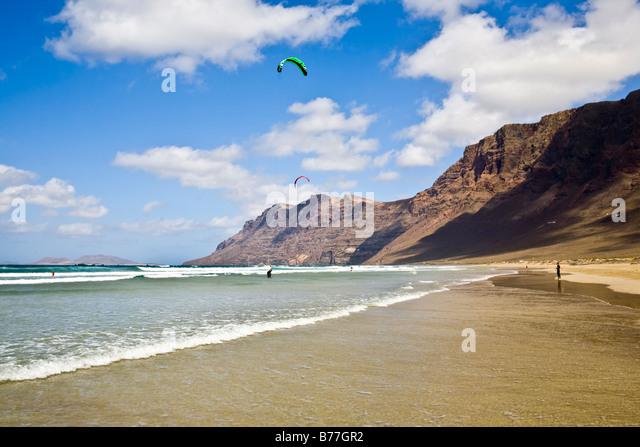 Playa de Famara risco de famara beach Mountain sand rocks reflection Lanzarote Canary Islands Spain - Stock Image