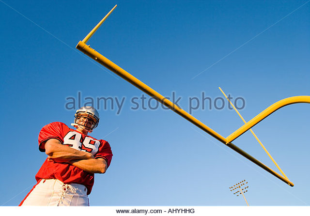 American football player, in red football strip and protective helmet, standing below goal post, arms folded, portrait - Stock Image