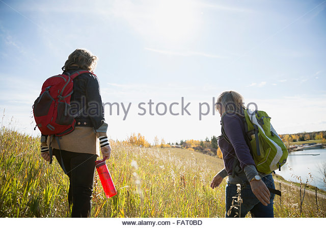 Women with backpacks hiking in sunny autumn field - Stock Image