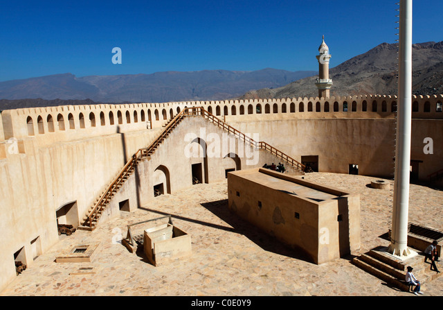 Tourists visit the gunnery platform in Nizwa Fort in Oman. - Stock Image