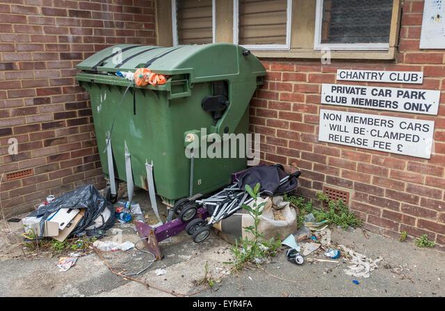 Overflowing rubbish dumped outside wheelie bin - Stock Image