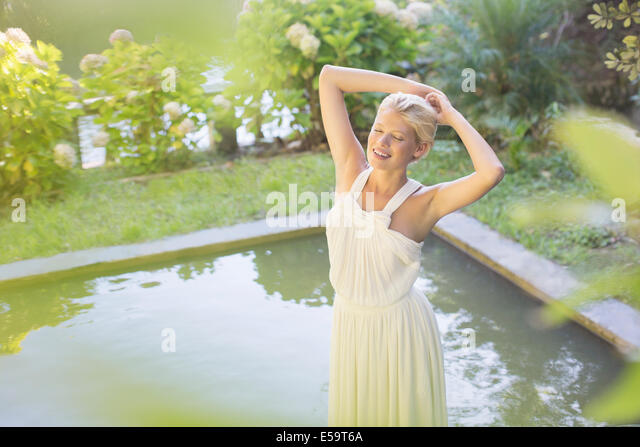 Woman standing by pool outdoors - Stock Image