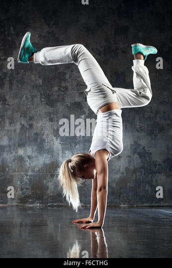Young woman modern dancer standing on hands. On stone wall background. - Stock Image