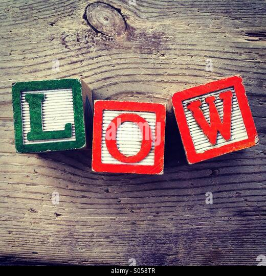 It's a photo of 3 wood cubes toy with letters that form the word LOW - Stock Image