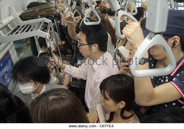 Tokyo Japan Ikebukuro JR Ikebukuro Station Yamanote Line Asian man woman crowded standing commuters train car strap - Stock Image