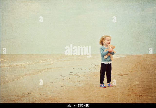 Little girl with teddy bear standing on beach - Stock-Bilder