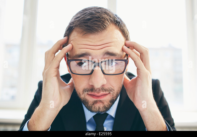 Frustrated businessman in eyeglasses touching his head - Stock Image