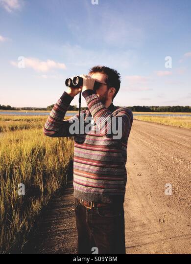A man birdwatching by a salt marsh in Connecticut, USA. - Stock-Bilder
