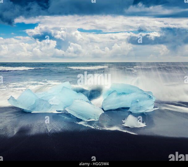 Blocks of ice washed by the waves on Jokulsarlon beach. Dramatic summer morning in Vatnajokull National Park, southeast - Stock Image