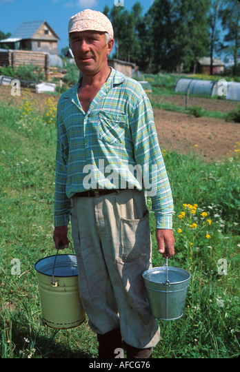 Russia former Soviet Union Irma resident carries water to garden country dacha beyond - Stock Image
