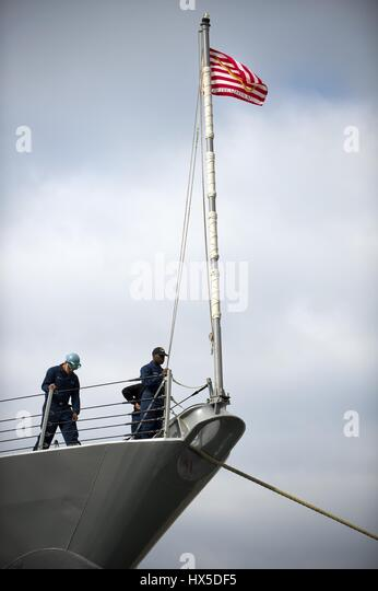 A Sailor lowers the Navy jack aboard the Arleigh Burke-class guided-missile destroyer USS Preble as it prepares - Stock Image