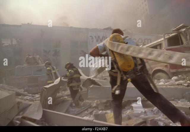 Fire fighters hauling a hose through rubble on September 11th, following terrorist attack on World Trade Center. - Stock-Bilder
