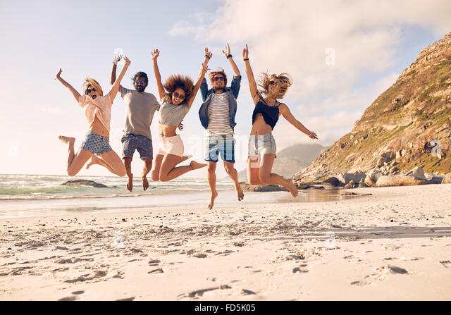 Group of friends together on the beach having fun. Happy young people jumping on the beach. Group of friends enjoying - Stock Image
