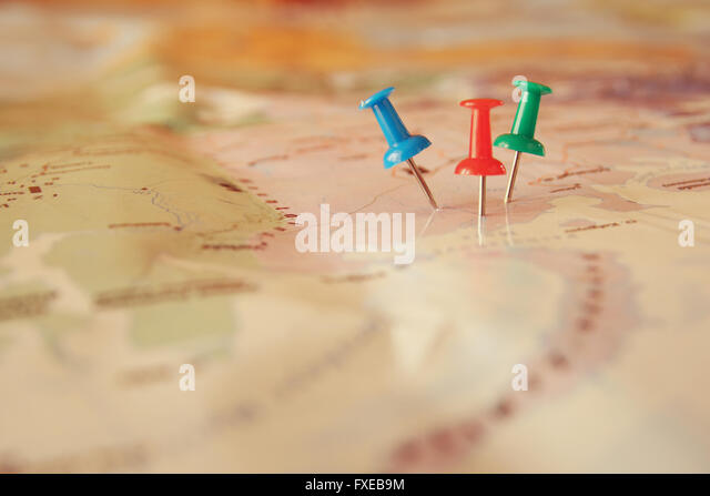 pins attached to map, showing location or travel destination . retro style image. selective focus. - Stock Image